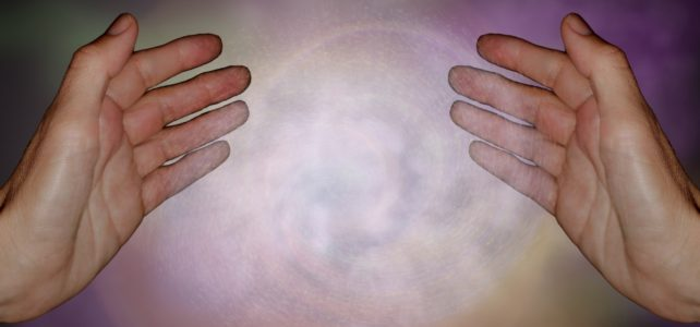 Reiki hands with white energy between them