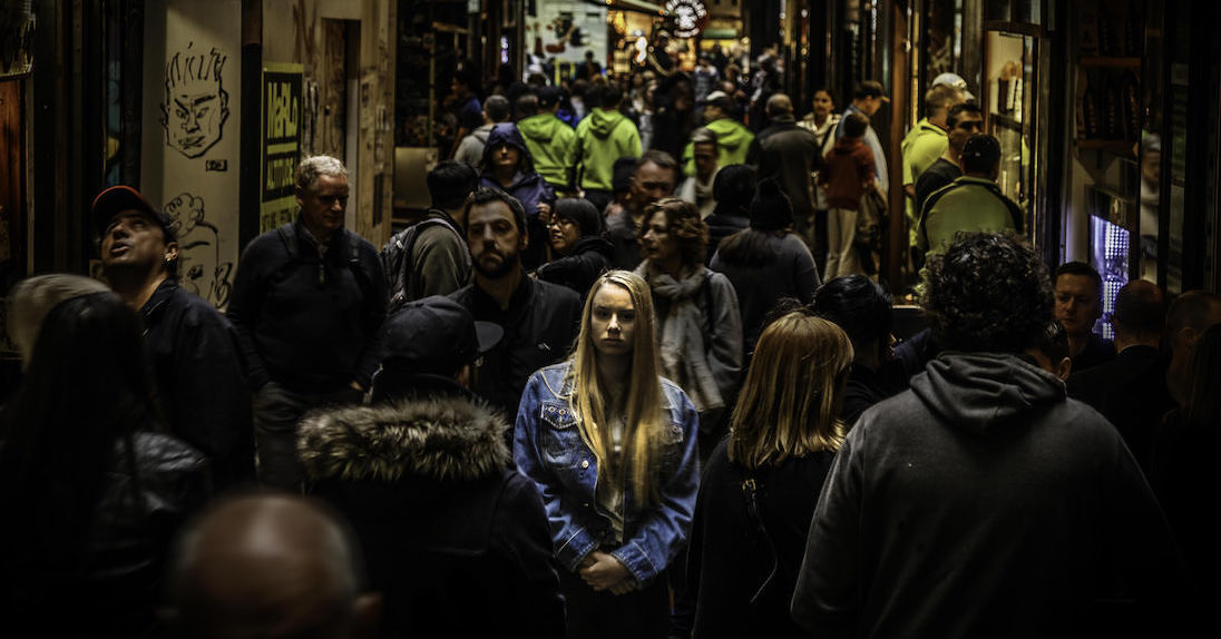 Woman standing alone in the light amougst dark crowded busy street; grief is lonely